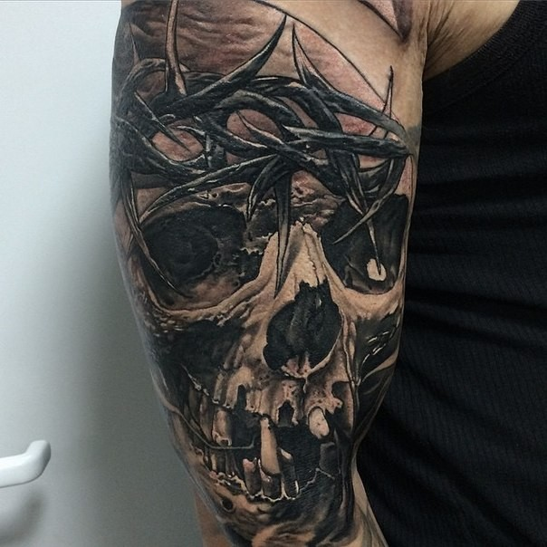 Black and gray style detailed hand tattoo of human skull with vine