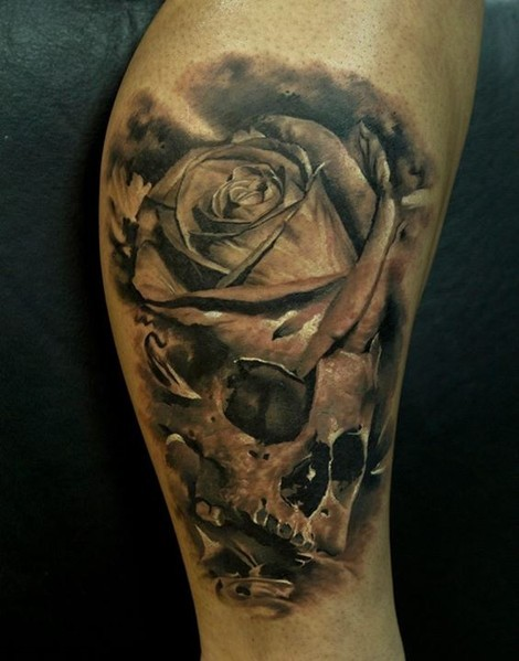 Black and gray style detailed human skull with rose