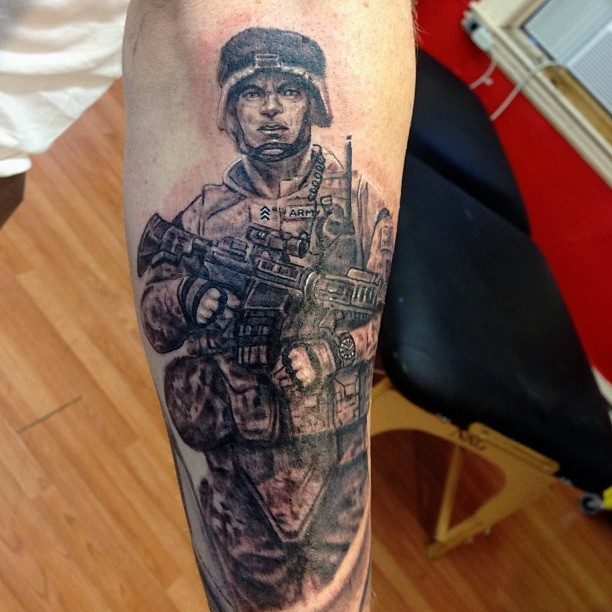 Black and gray style detailed leg tattoo of American soldier