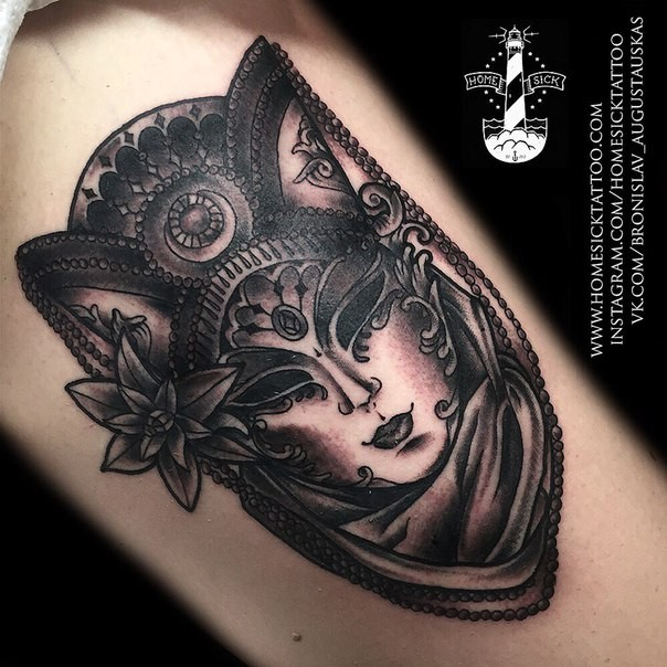 Black and gray style detailed looking arm tattoo of mystical mask with flower and ornaments