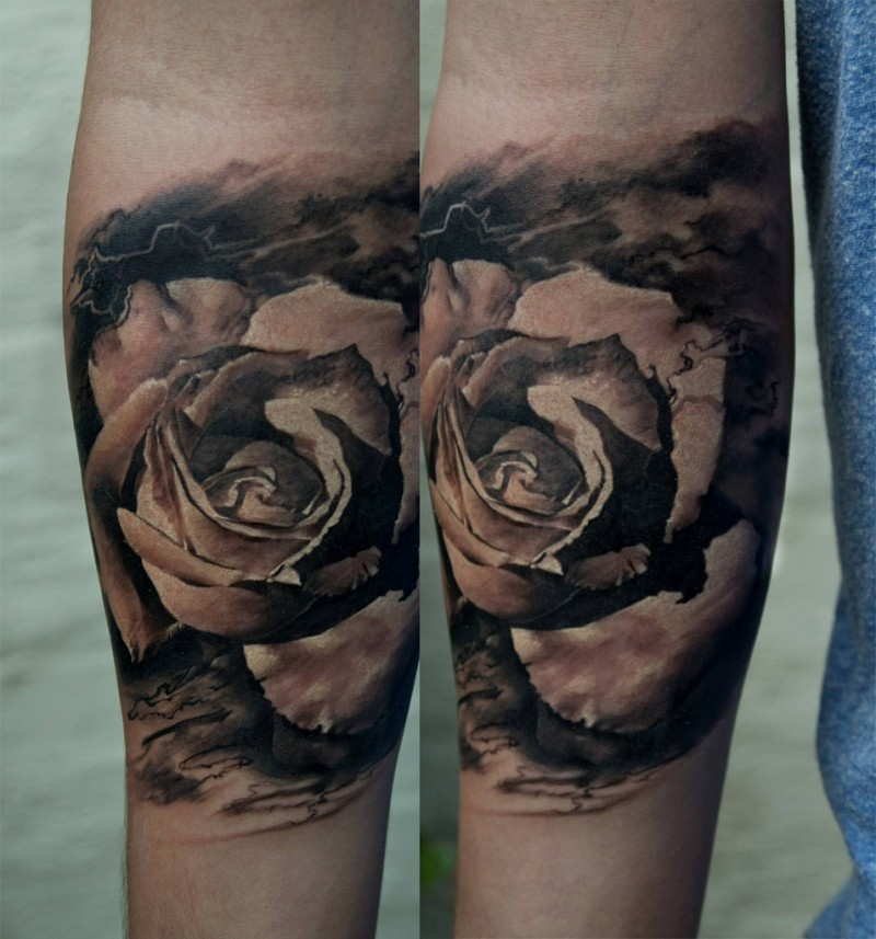 Black and gray style detailed looking arm tattoo of rose flower