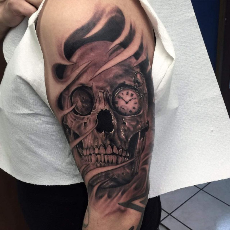 Black and gray style detailed shoulder tattoo of human skull with clock