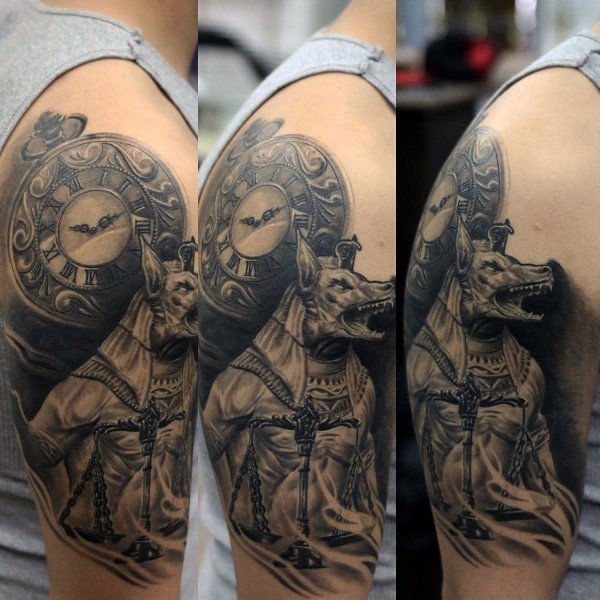 Black and gray style detailed shoulder tattoo of evil Egypt God with clock