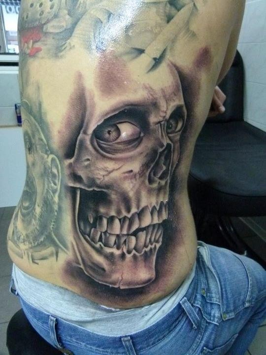 Black and gray style detailed side tattoo of human skull with eyes