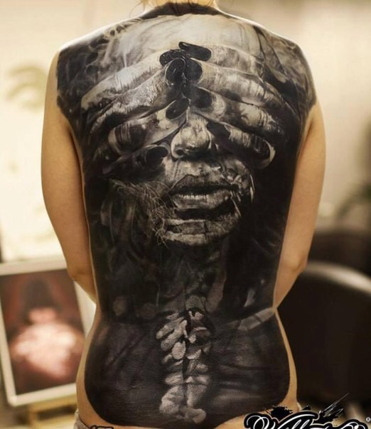Black and gray style detailed whole back tattoo of woman face with hands