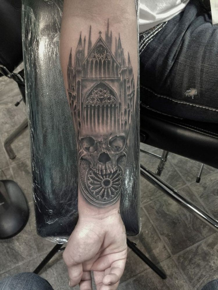 Black and gray style forearm tattoo of old cathedral with skull