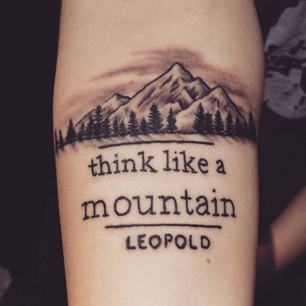 Black and gray style forearm tattoo of mountain with lettering