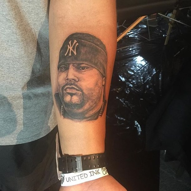 Black and gray style forearm tattoo of man portrait
