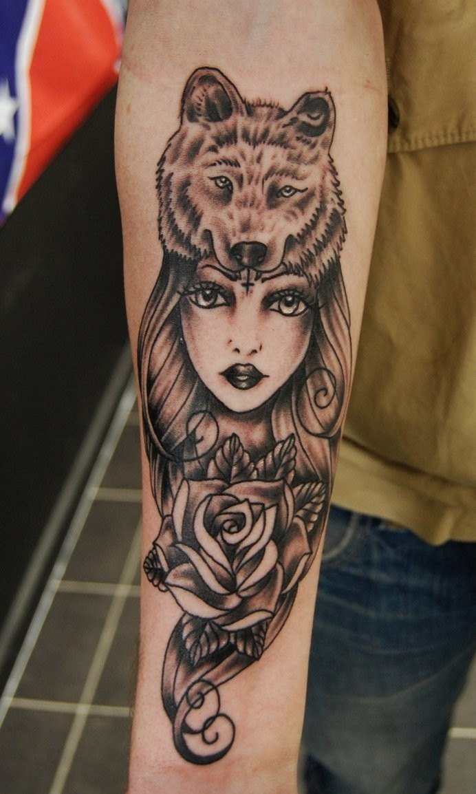 Black and gray style forearm tattoo of woman with rose and wolf helmet