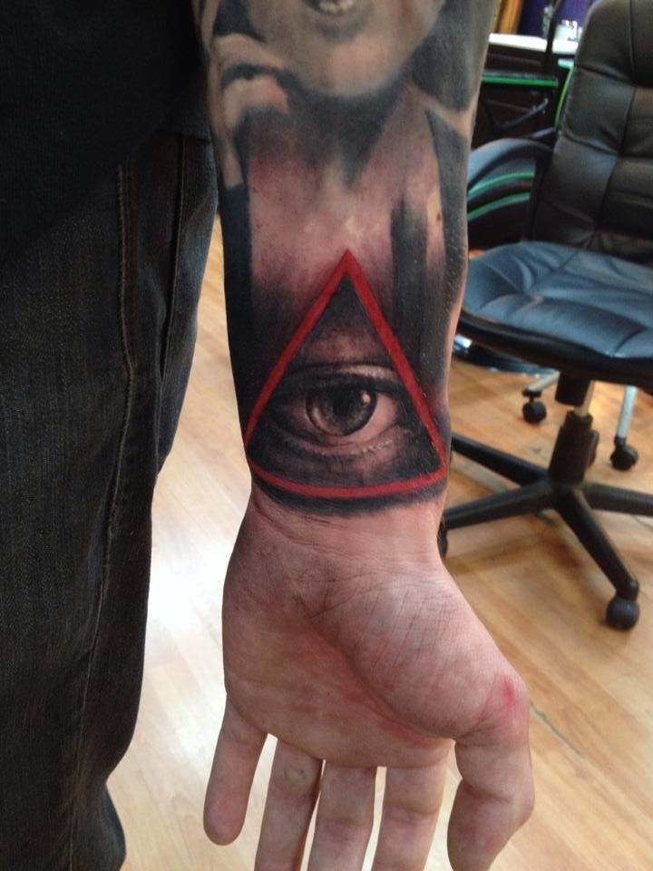 Black and gray style human eye tattoo on wrist with red triangle