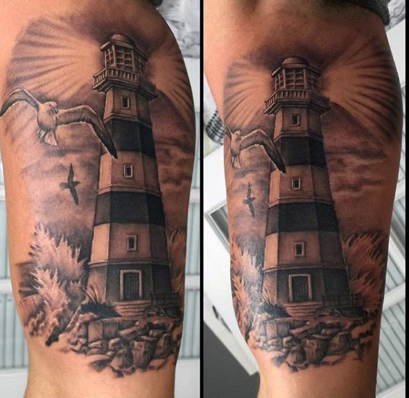 Black and gray style large biceps tattoo of lighthouse with seagulls