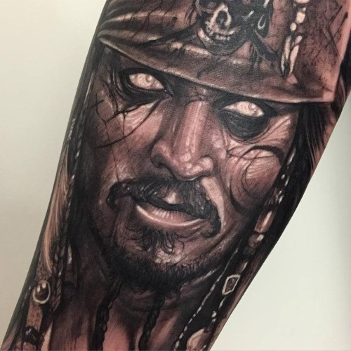 Black and gray style large forearm tattoo of demonic Jack Sparrow portrait