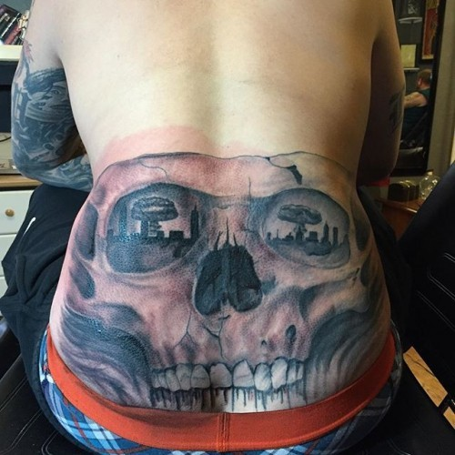 Black and gray style magnificent looking skull tattoo on back with bomb blast