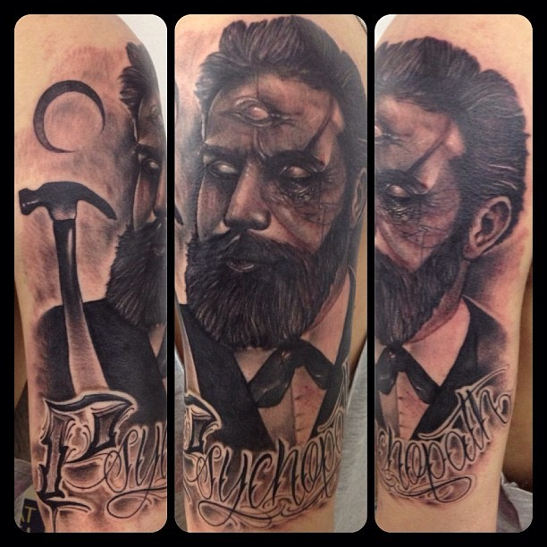 Black and gray style mystic man with third eye and lettering tattoo on shoulder