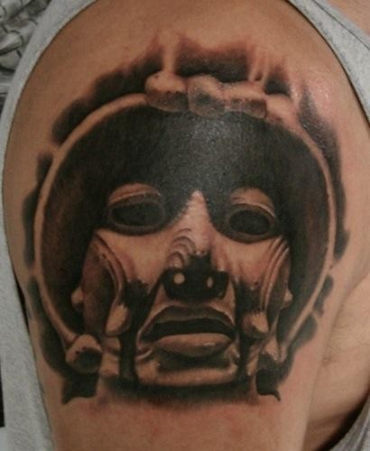 Black and gray style shoulder tattoo of creepy mask