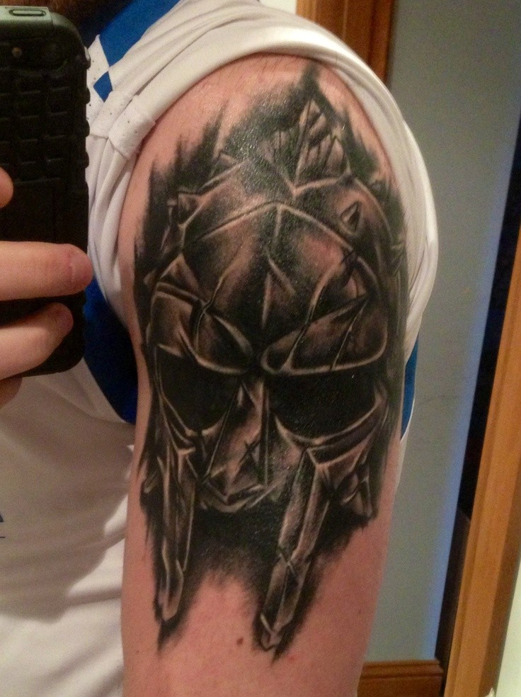 Black and gray style shoulder tattoo of gladiators helmet