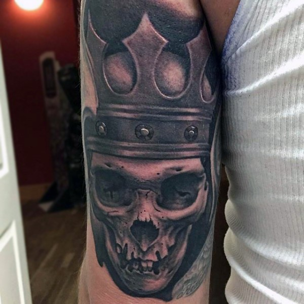 Black and gray style skull tattoo on arm with crown
