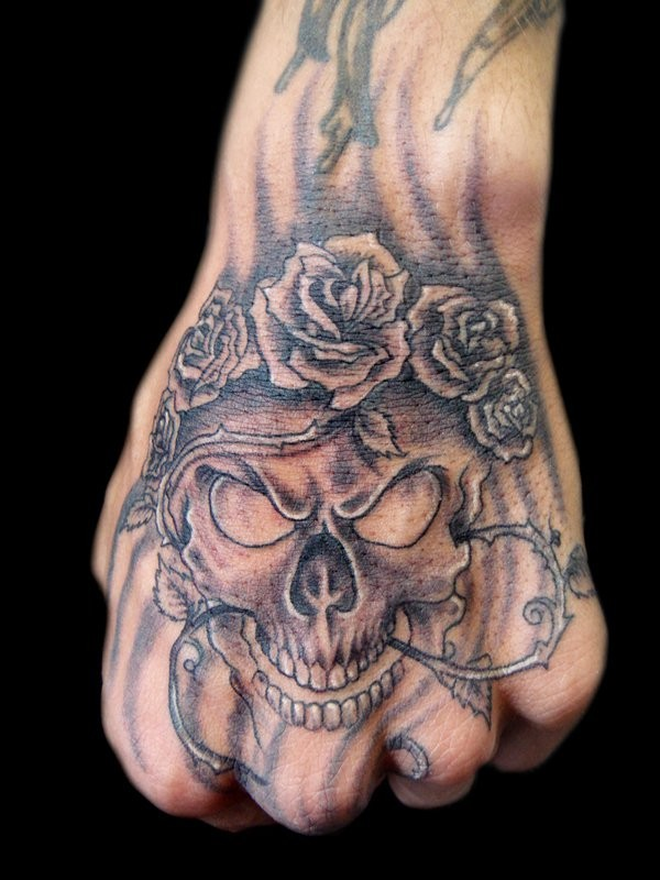 Black and gray style small creepy human skull with roses and vine tattoo on hand