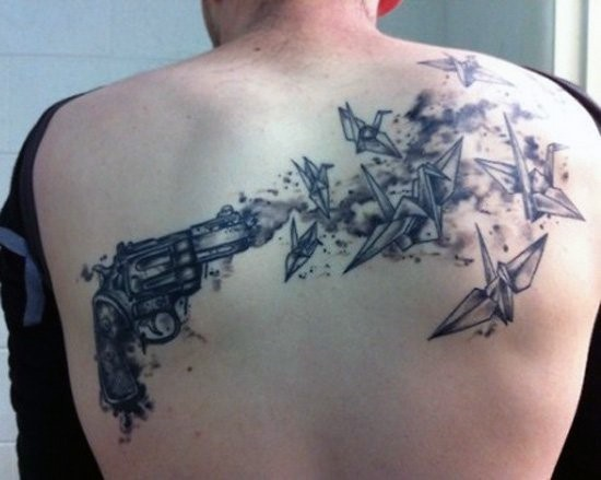 Black and gray style upper back tattoo of small pistol and paper birds