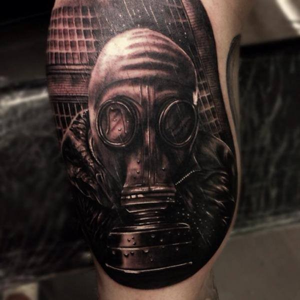 Black and gray style very detailed tattoo of man in gas mask in forest