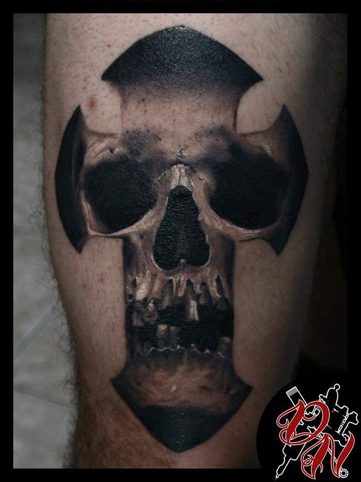 Black and grey skull in cross tattoo