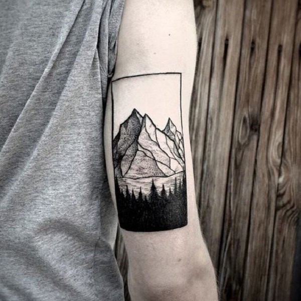 Black and white arm tattoo of mountains with forest