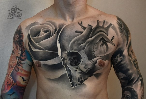 Black and white chest tattoo of human skull with heart and rose