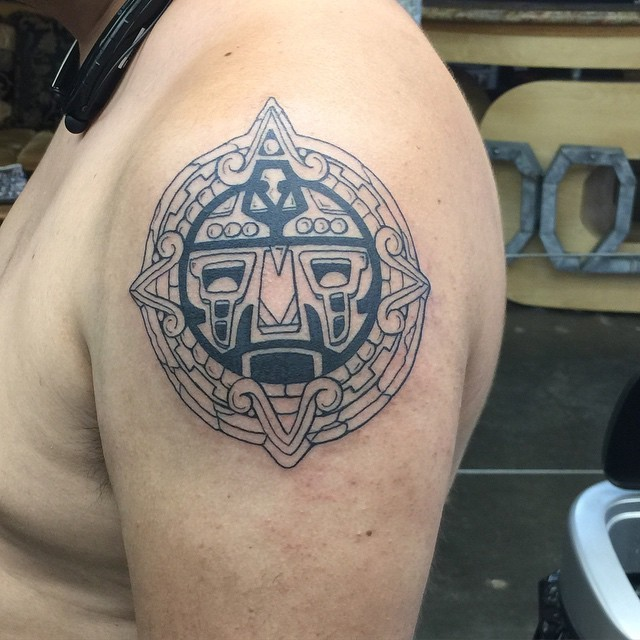 Black and white circle shaped shoulder tattoo of ancient stone tablet