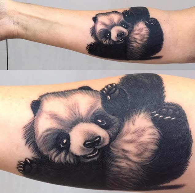 Black and white cute baby panda in playing mood tattoo on forearm