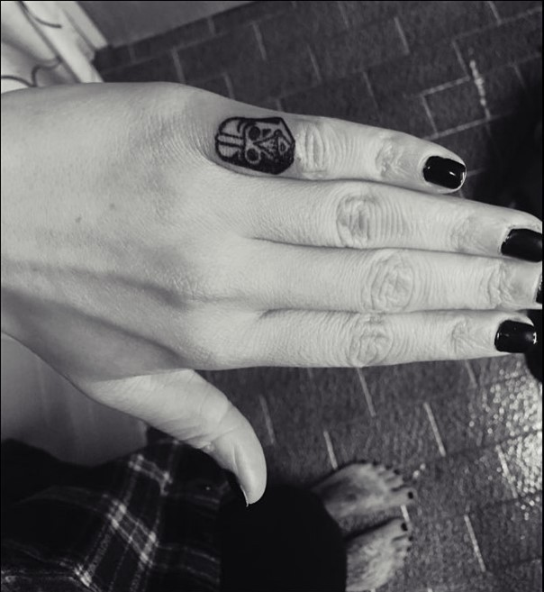 Black and white Darth Vader&quots helmet tattoo on little finger