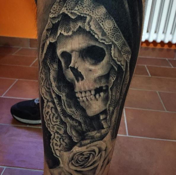 Black and white detailed leg tattoo of human skeleton in hood with rose