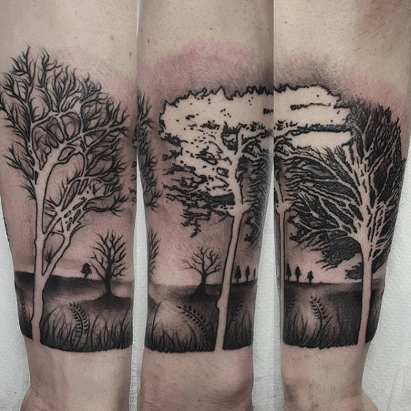 Black and white forearm tattoo of forest trees