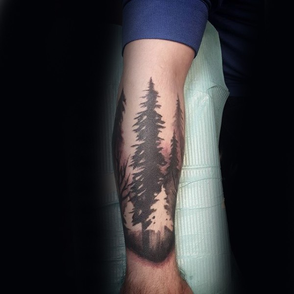 Black and white forearm tattoo of large forest trees