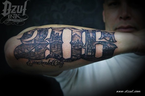 Black and white forearm tattoo of number stylized with city sights and lettering