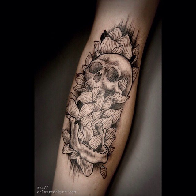 Black and white human skull with flowers tattoo on forearm length