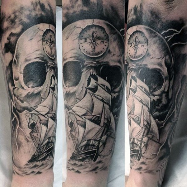 Black and white massive nautical tattoo with skull and sailing ship on arm
