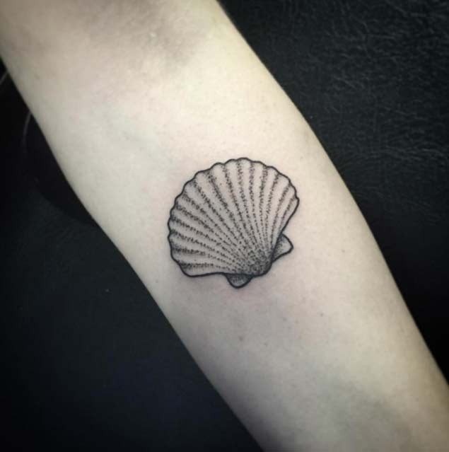 Black and white shell tattoo on forearm area