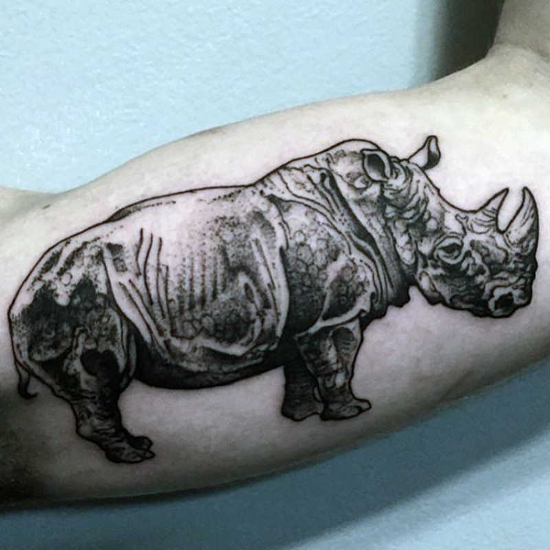 Black and white small natural looking biceps tattoo of rhino