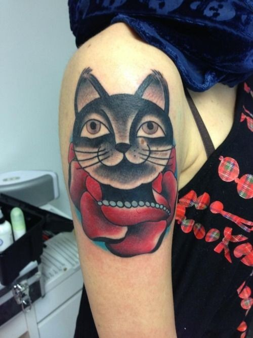 Black cat and red rose tattoo on shoulder