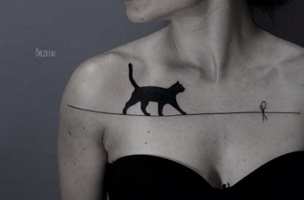 Black cat walking on the stretched thread realistic tattoo on collarbone area