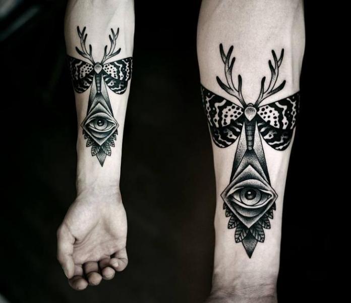 dotwork nero occhio falena e corna avambraccio tatuaggio