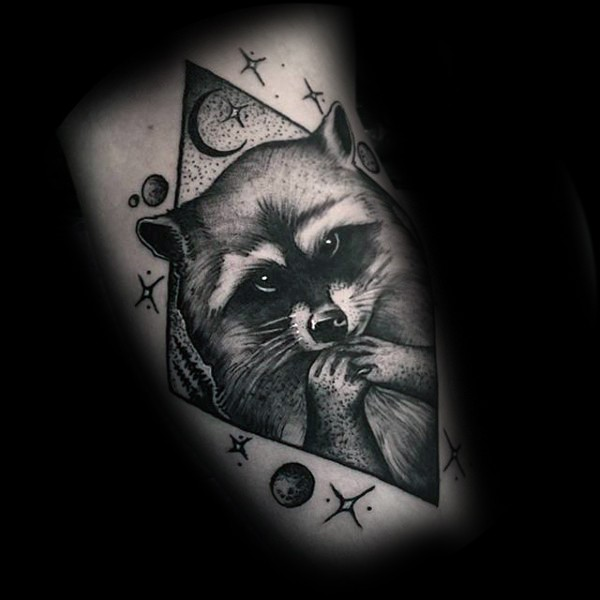 Black engraving style tattoo of raccoon with stars and planets