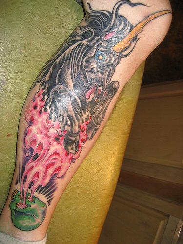 Black evil unicorn and green skull leg tattoo