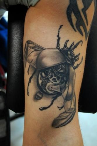 Black gray biomechanical bug tattoo on arm