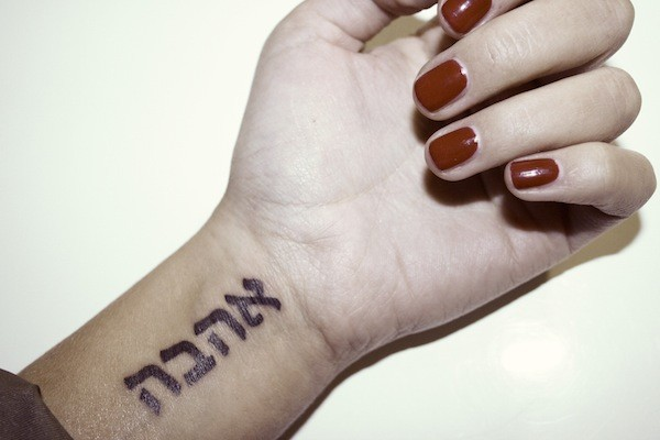 Black ink Arabic lettering tattoo on woman&quots wrist in homemade style