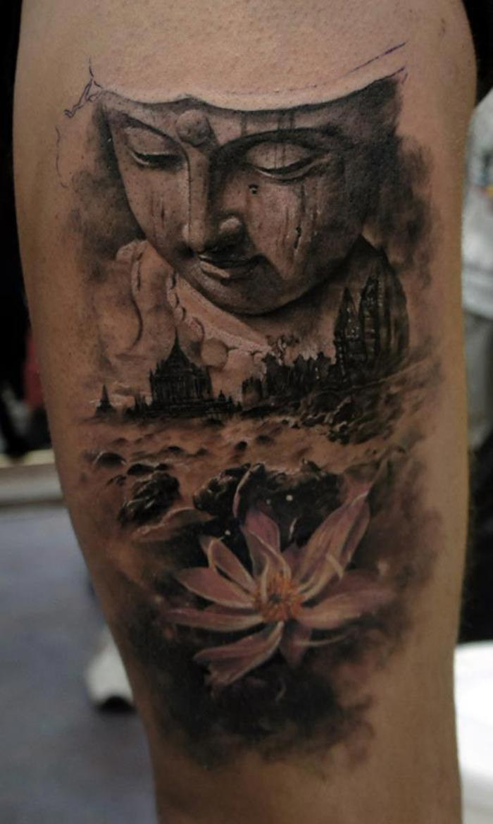 Black ink arm tattoo of Buddha statue with old city