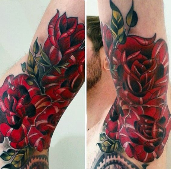Black ink arm tattoo of large red roses with leaves