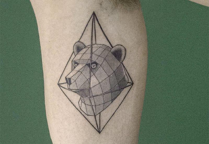 Black ink biceps tattoo of bear head with rhombus
