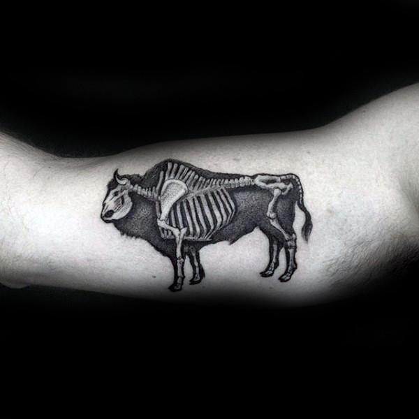 Black ink biceps tattoo of grunting ox skeleton