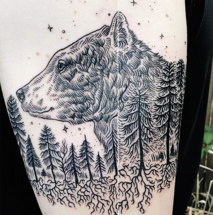 Black ink big amazing looking bear head with forest tattoo on arm